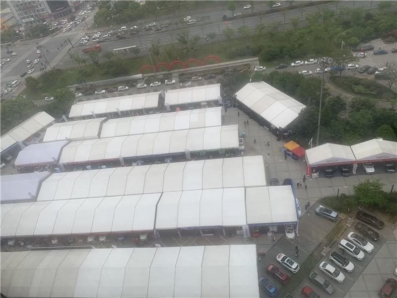 Uma tenda de formato combinada com um salão de automóveis