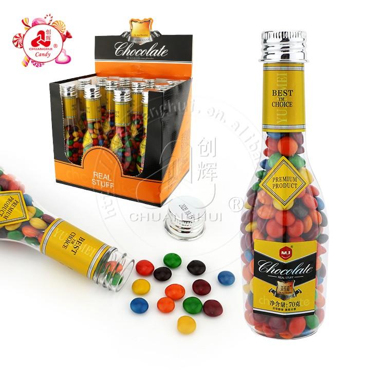 Emballage de bouteille de vin avec des mini bonbons colorés au chocolat enrobés de sucre