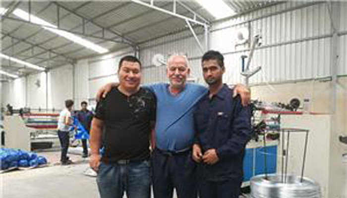 Our technician and interpreter are debugging chain link fence machine in Qatar customer